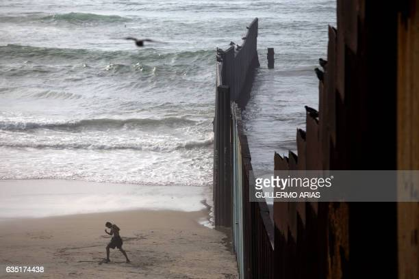 A man walks next to the Mexico US border at Playas de Tijuana in northwestern Mexico on February 13 2017 This image is part of an ongoing AFP photo...