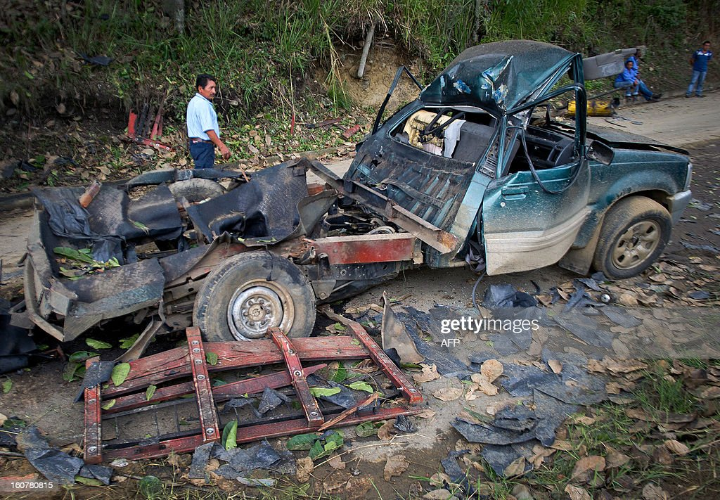 A man walks next to the remains of a car bomb in El Palo, department of Cauca, Colombia, on February 5, 2013. Two car bombs were detonated allegedly by Revolutionary Armed Forces of Colombia (FARC) guerrillas at a military checkpoint in southwestern Colombia Tuesday, killing a civilian and a soldier, and injuring three soldiers.