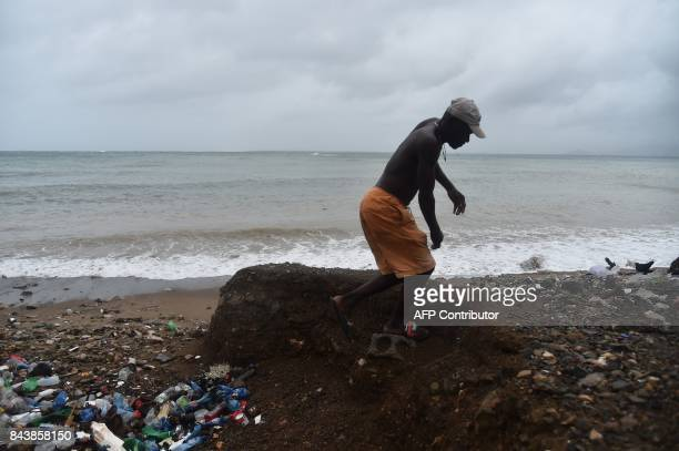 A man walks next to the sea close to a fishing cove in CapHaitien on September 7 as Hurricane Irma approaches Irma was packing maximum sustained...
