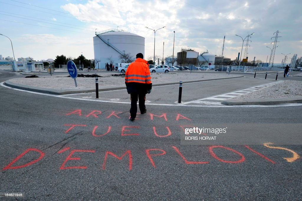 A man walks next to the slogan ''Arkema job killers'' written on the sidewalk as employees of Kem One, a French company specialized in chlorochemicals and vinyl products, block the access to their company in Lavera, southern France, on March 25, 2013 after French unions announced the company's cessation of payments. 350 jobs could be cut on the Lavera site. AFP PHOTO / BORIS HORVAT