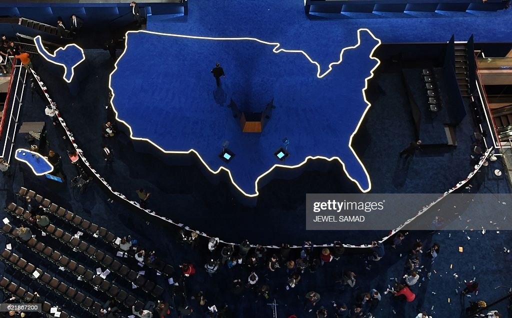 A man walks off an empty stage after Democratic presidential nominee Hillary Clinton did not arrive to speak during election night at the Jacob K. Javits Convention Center in New York on November 9, 2016. / AFP / Jewel SAMAD
