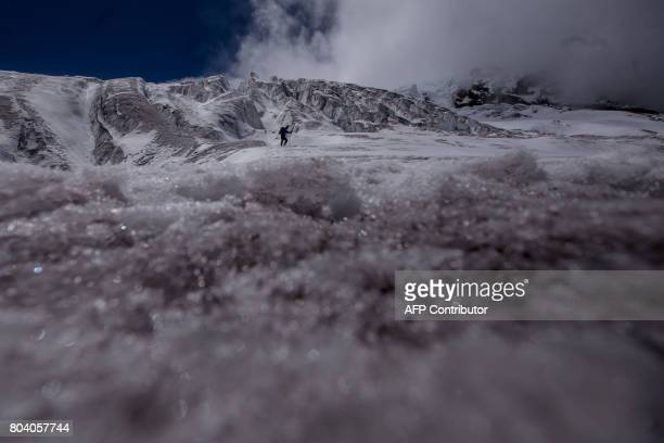 TOPSHOT A man walks on a glacier on Antisana Volcano 50km east of Quito Ecuador on June 29 2017 At the foot of a rapidly melting glacier several...