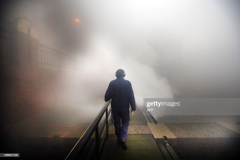 A man walks on a platform as steam rises from the boilers of a pumping-station in Lemmer, the northern Netherlands, on December 24, 2012. The station pumps excess water from the northern province to a nearby lake. The authorities decided to turn on the pumping-station due to expected heavy rainfall.
