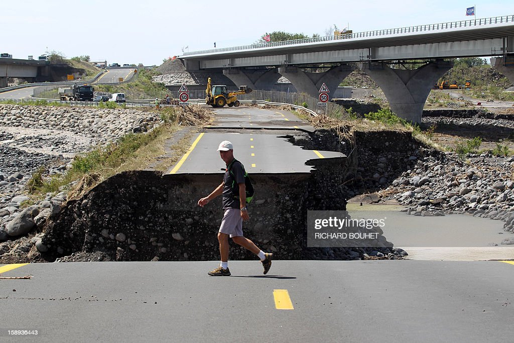 A man walks on a remaining piece of road crossing the river that links Saint Louis de la Reunion with Saint Pierre on January 4, 2013 near Saint Louis, on the French island of La Reunion, following the passing of cyclone Dumile. Winds of up to 180 kilometres per hour (110 miles per hour) and torrential rain caused extensive damage to the electricity network after cyclone Dumile passed within 90 kilometres of the island's west coast at around 0900 GMT. AFP PHOTO / RICHARD BOUHET