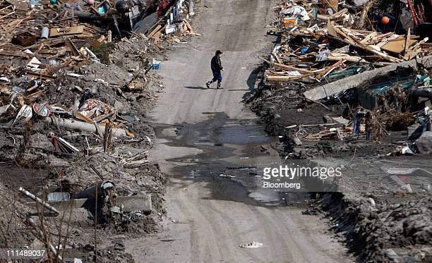A man walks on a road after tsunami debris was removed in Otsuchi town Iwate prefecture Japan on Sunday April 3 2011 Japan begins forging a road map...