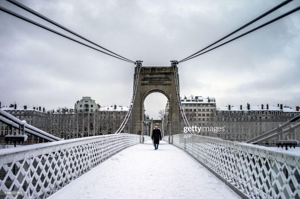 A man walks on a snow covered bridge in Lyon on January 15, 2012. AFP PHOTO / JEFF PACHOUD