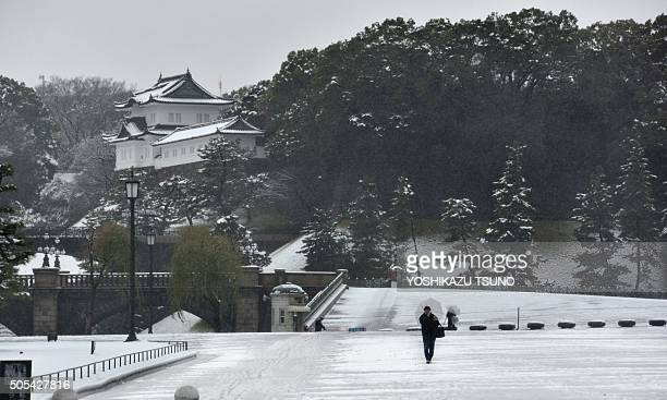 A man walks on a snow covered field in front of the Imperial Palace in Tokyo on January 18 2016 Heavy snow blanketed Tokyo metropolitan area and...