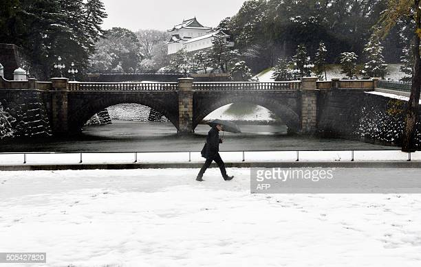 TOPSHOT A man walks on a snow covered field in front of the Imperial Palace in Tokyo on January 18 2016 Heavy snow blanketed Tokyo metropolitan area...