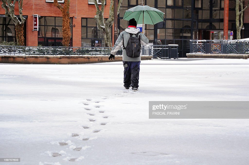 A man walks on a snow covered square on January 20, 2013 in Toulouse southern France, after heavy snow falls. AFP PHOTO PHOTO / PASCAL PAVANI