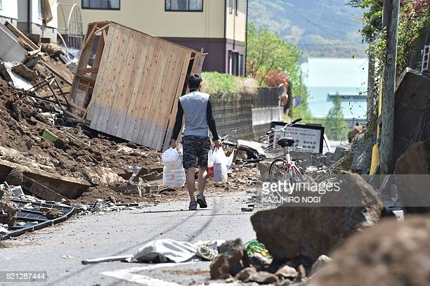 TOPSHOT A man walks on a street covered with rubble in the town of Mashiki Kumamoto prefecture on April 15 2016 A strong 65magnitude earthquake hit...
