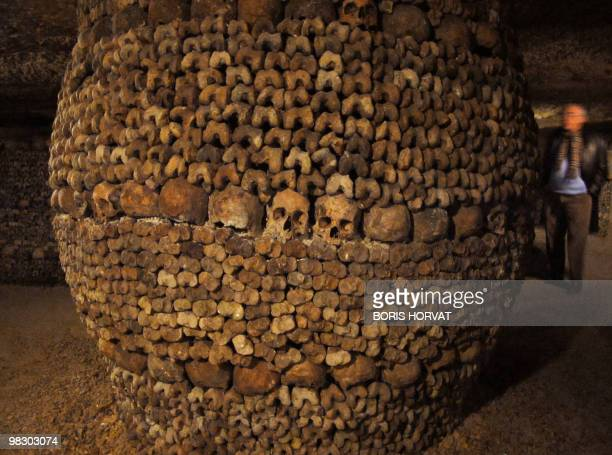 A man walks on April 3 2010 next to a column made of skulls and bones at the Catacombs of Paris These subterrainian quarries had been used to store...