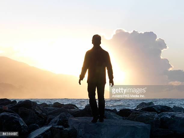 Man walks on boulders towards open sea
