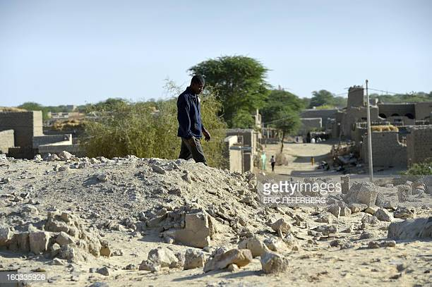 A man walks on January 29 2013 in the ruins of the Sidi Moctar shrine which was destroyed by Islamists in July in a cemetery of Timbuktu Frenchled...