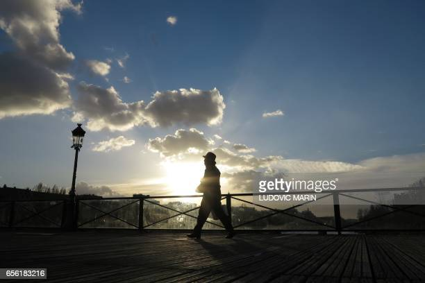 A man walks on Le pont des Arts over the river Seine at sunset on March 31 2017 in Paris / AFP PHOTO / Ludovic MARIN