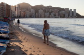 A man walks on Levante Beach in the early morning on August 10 2013 in Benidorm Spain Benidorm is one of Europe's top package holiday destinations...