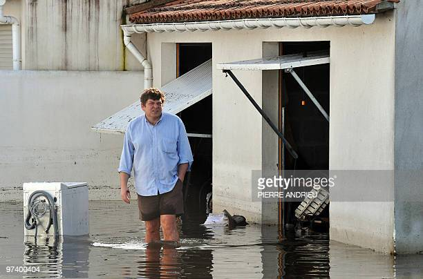 A man walks on March 2 2010 on the Re island in his garden flooded after a storm dubbed 'Xynthia' which killed 51 people unleashed gale force winds...