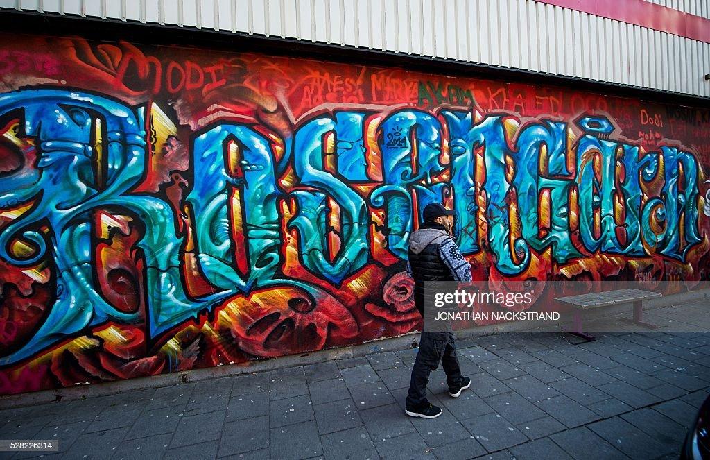 A man walks on May 2, 2016 next to a big graffiti wall with the name of theneighbourhood of Rosengaard in Malmoe, where Swedish national team football player, Zlatan Ibrahimovic grew up. / AFP / JONATHAN