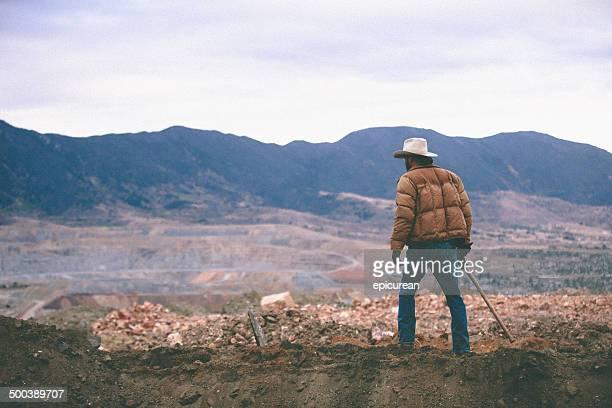 Homme marchant sur mound de travail site entouré de moutains