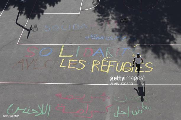 A man walks on the basketball court of disused secondary school GuillaumeBude on which is painted in French and Arabic 'Solidarity with refugees' and...