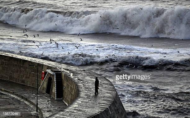 A man walks on the Cobb as storm waves break behind on December 13 2011 in Lyme Regis England The Met Office has issued severe weather warnings for...