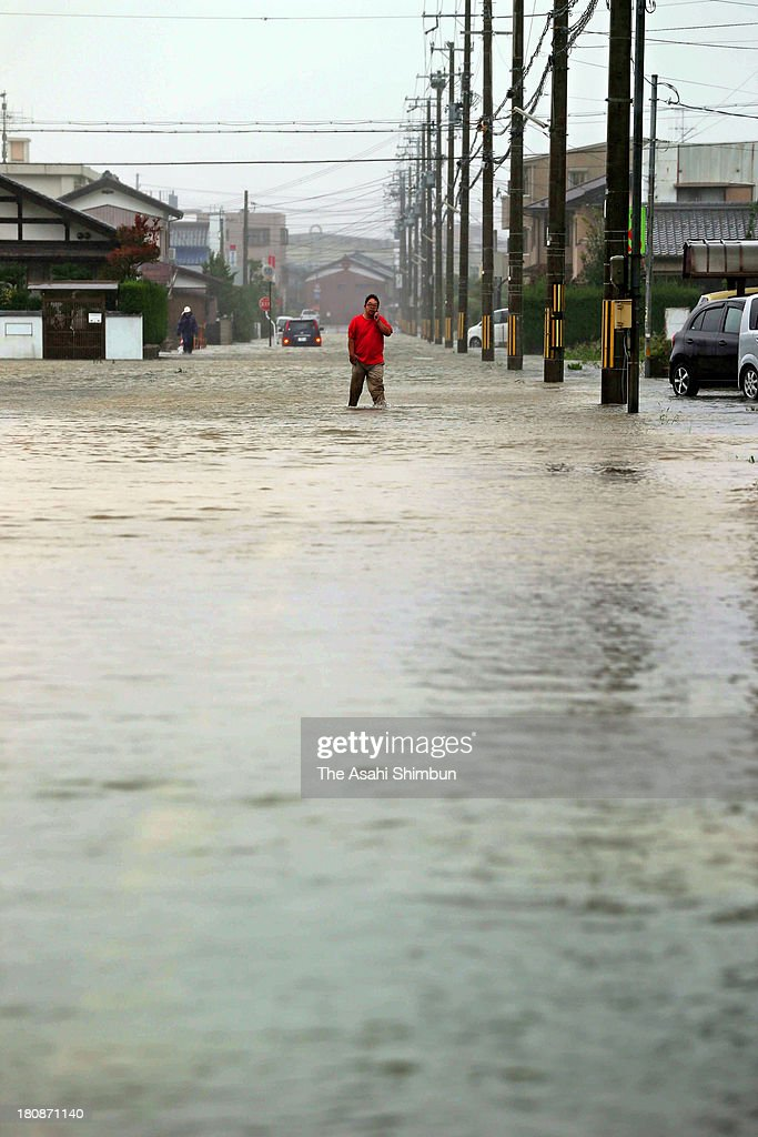 A man walks on the flooded road triggered by typhoon ManYi approaching on September 16 2013 in Obama Fukui Japan The storm hit land near Toyohashi...