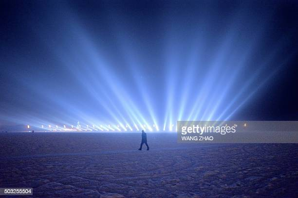 TOPSHOT A man walks on the frozen Songhua river beside the Harbin international ice and snow festival in Harbin northeast China's Heilongjiang...
