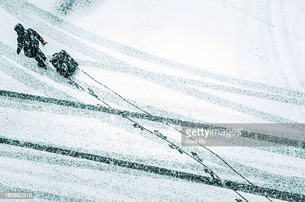 Man walks on the snowy street with his luggage