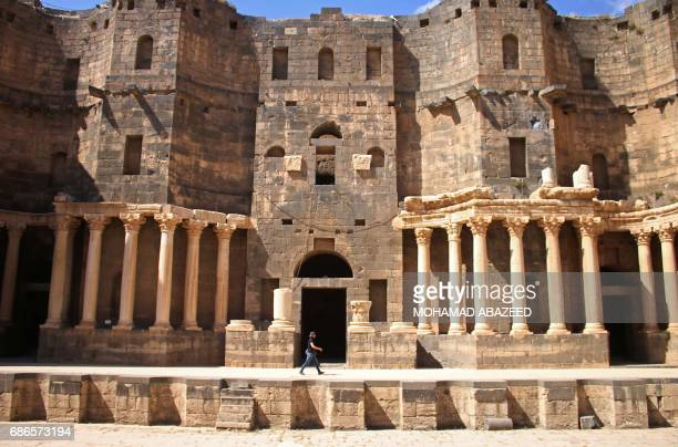 A man walks on the stage at the ancient Roman amphitheatre of Bosra alSham which is listed as a UNESCO world heritage site in the southern Syrian...