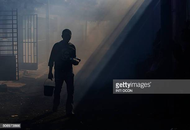 A man walks on the street while Health Ministry workers fumigate against the Aedes aegypti mosquito to prevent the spread of the Zika and Chikungunya...