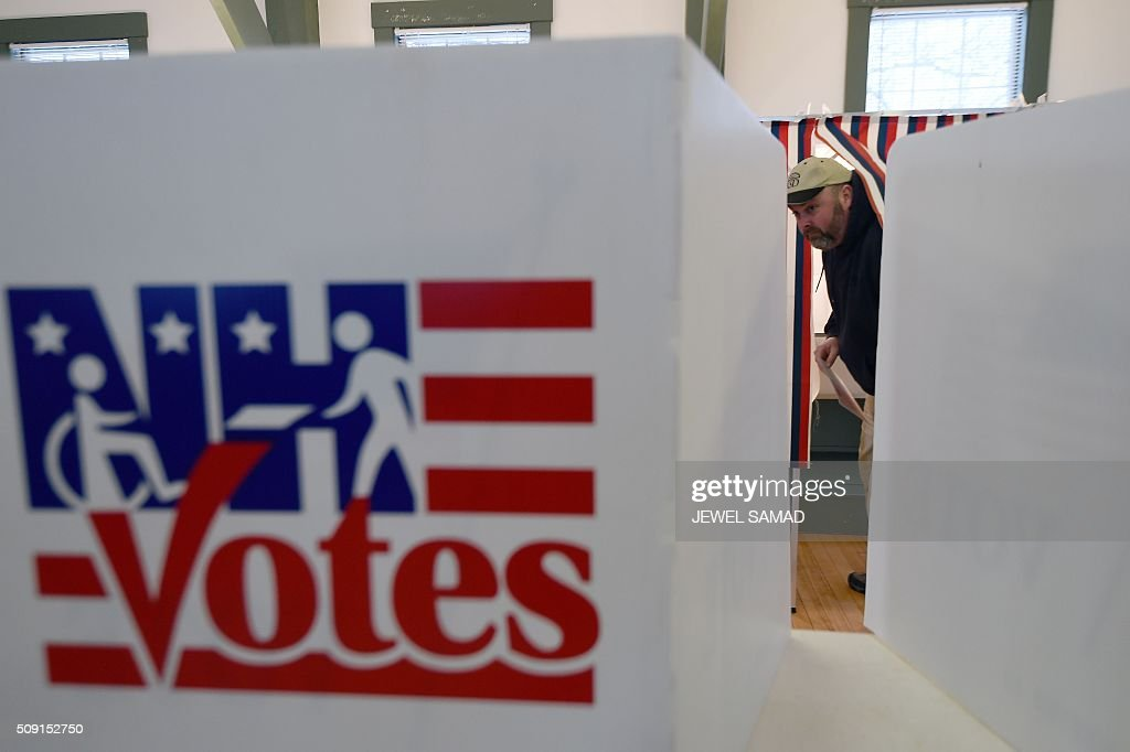 A man walks out of a booth with his ballot for the first US presidential primary at the town hall in Canterbury, New Hampshire, on February 9, 2016. New Hampshire began voting on February 9 in the first US presidential primary with Republican Donald Trump calling on supporters to propel him to victory and Democrat Bernie Sanders primed to upstage Hillary Clinton. The northeastern state, home to just 1.3 million people, sets the tone for the primaries and could shake out a crowded Republican field of candidates pitting Trump and arch-conservative Senator Ted Cruz against more establishment candidates led by Senator Marco Rubio. / AFP / Jewel Samad