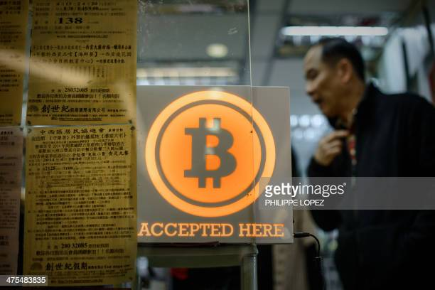 A man walks out of a shop displaying a bitcoin sign during the opening ceremony of the first bitcoin retail shop in Hong Kong on February 28 2014...