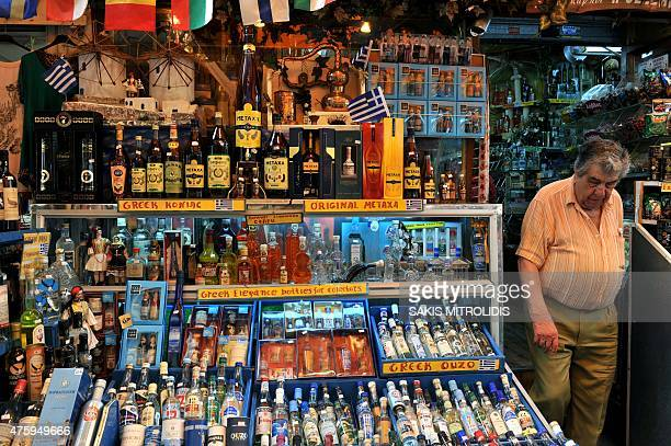 A man walks out of a shop displaying bottles of the popular Greek aperitif Ouzo and the Greek cognac Metaxa at a shop in Thessaloniki on 5 June 2015...