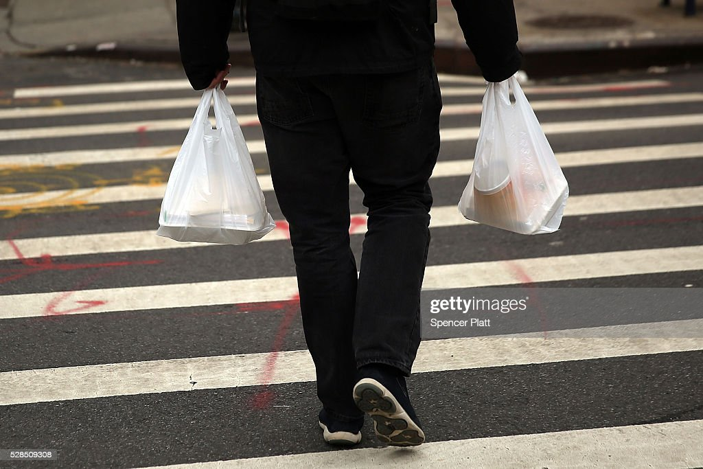 A man walks out of a store with a plastic bags on May 05, 2016 in New York City. New York's City Council is scheduled to vote Thursday on a bill that would require most stores to charge five cents per bag in an effort to cut down on plastic waste. New York's sanitation department estimates that every year 10 billion bags are thrown in the trash.