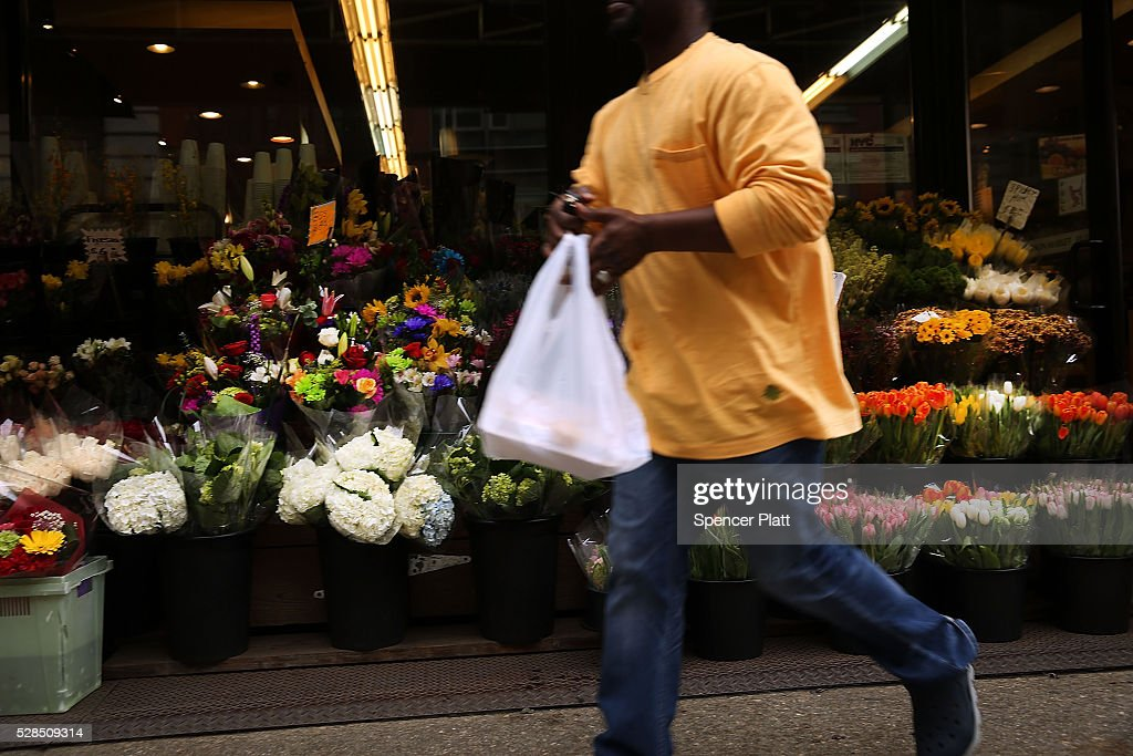 A man walks out of a supermarket with a plastic bag on May 05, 2016 in New York City. New York's City Council is scheduled to vote Thursday on a bill that would require most stores to charge five cents per bag in an effort to cut down on plastic waste. New York's sanitation department estimates that every year 10 billion bags are thrown in the trash.