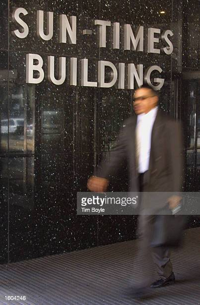 A man walks out of the Chicago SunTimes building July 25 2001 in front of the Chicago SunTimes building in downtown Chicago Donald Trump and the...
