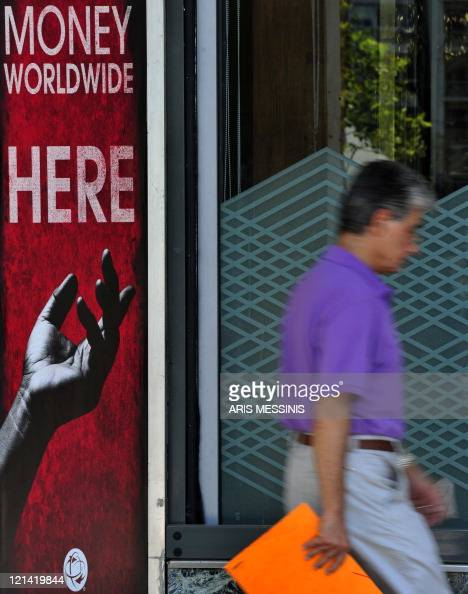 A man walks outside a money exchange store in central Athens on August 08 2011 The Athens Stock Exchange opened with a loss and went on falling to...