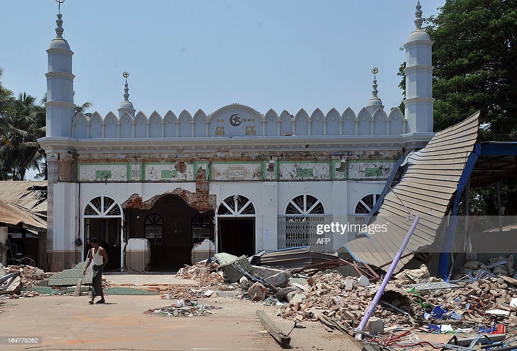 A man walks outside a partially-destroyed mosque after sectarian violence spread through central Myanmar, in Gyobingauk, Bago division on March 28, 2013. Myanmar's Muslim leaders have appealed to President Thein Sein to take swift action to quell religious violence, accusing security forces of standing by as rioters went on a rampage. AFP PHOTO/Ye Aung THU
