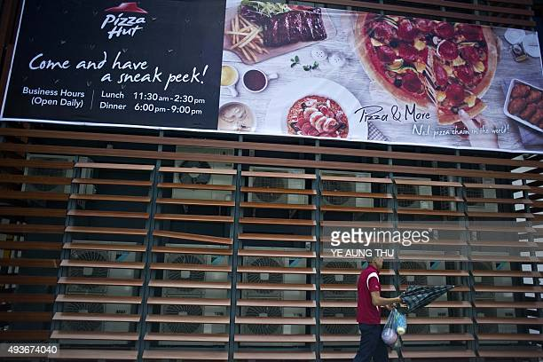 A man walks outside Pizza Hut's first restaurant in Yangon on October 22 2015 Pizza Hut is to open its first restaurant in Yangon the latest major...