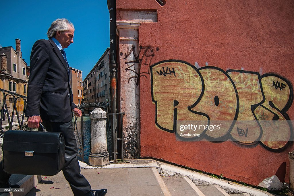 A man walks over a bridge past some graffiti on a wall and on the marble on May 27, 2016 in Venice, Italy. In recent years, graffiti and street art has appeared in Venice, with some complaining that it is ruining the walls and palaces of the city.