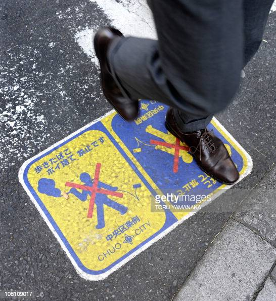 A man walks over a sign to ban smoking and throwing cigarette butt out on the street in Tokyo on January 18 2011 AFP PHOTO/Toru YAMANAKA