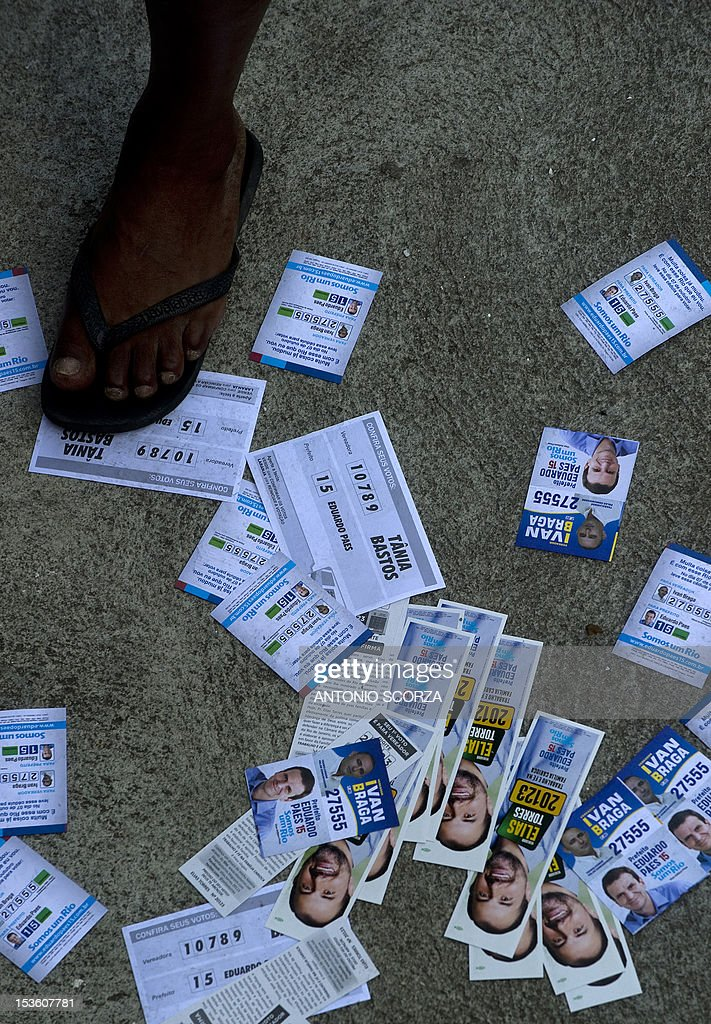 A man walks over pamphlets as he heads to a polling station in Rio de Janeiro's Rocinha shantytown, Brazil, on October 7, 2012 during the nationwide municipal elections. Nearly 139 million Brazilians are registered to elect 5,561 mayors and 48,000 municipal councilors among 450,000 candidates representing more than 20 political parties. AFP PHOTO/ANTONIO SCORZA