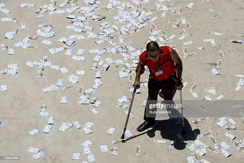 A man walks over pamphlets as he heads to a polling station in Rio de Janeiro's Rocinha shantytown on October 07, 2012 in Rio de Janeiro, Brazil.