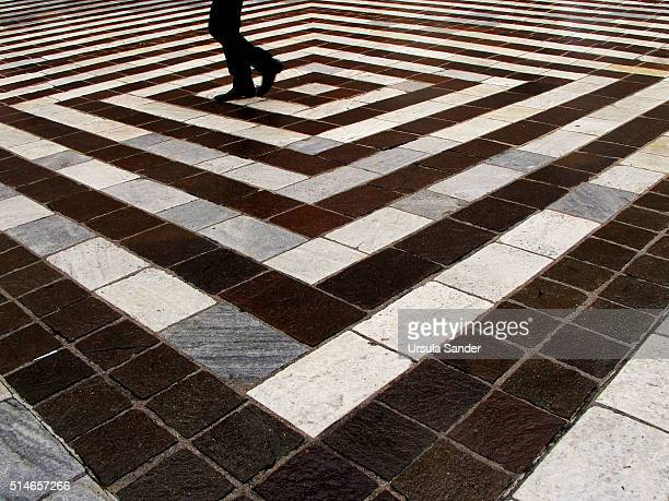 Man walks over rhombic pavement pattern built of black and white gray stripes