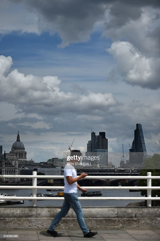 A man walks over Waterloo bridge with a backdrop of St Paul's Cathedral and buildings in City of London in central London on June 27, 2016. Britain began preparations to leave the European Union on Monday but said it would not be rushed into a quick exit, as markets plunged in the wake of a seismic referendum despite attempts to calm jitters. / AFP / BEN