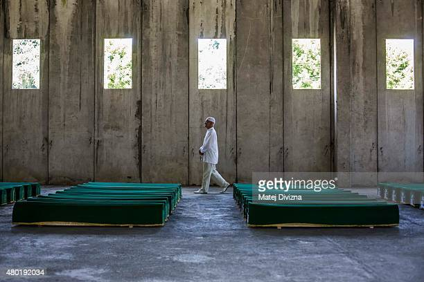 A man walks past 136 coffins of victims of the 1995 Srebrenica massacre in the hall at the Potocari cemetery and memorial near Srebrenica on July 10...