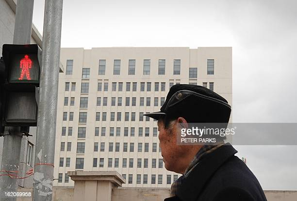 A man walks past a 12storey building alleged in a report on February 19 2013 by the Internet security firm Mandiant as the home of a Chinese...