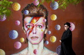 A man walks past a 3D wall portrait of British musician David Bowie created by Australian street artist James Cochran also known as Jimmy C in...
