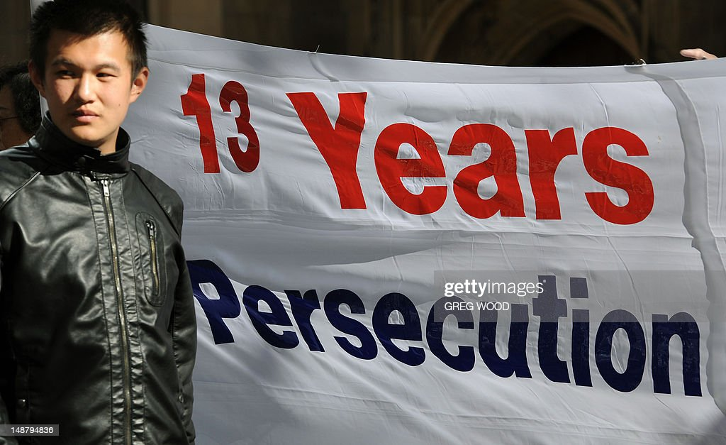 A man walks past a banner as practitioners of spiritual movement Falungong gather at Sydney's Town Hall Square on July 20, 2012. The group intends to present an open letter to the Sydney office of Australian Prime Minister Julia Gillard urging her to denounce what they say is a 13-year-long persecution of the spiritual practice in China. Falungong -- a movement loosely based on Buddhist, Taoist and Confucian philosophies -- enjoyed growing popularity among the Chinese in the 1990s, but was banned by China in 1999 after thousands of practitioners silently converged in Beijing to air their grievances, showing their organizational might. AFP PHOTO / Greg WOOD