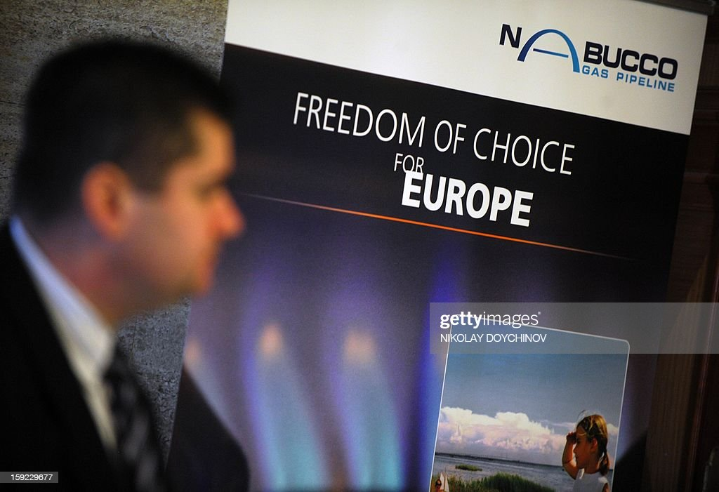 A man walks past a banner during a meeting of the shareholders of gas pipeline Nabucco West, in Sofia, on January 10, 2013. The consortium developing a huge gas field in Azerbaijan will decide by the end of June whether to pick EU's flagship Nabucco pipeline as its preferred transport route to Europe, a Nabucco representative said on January 10.