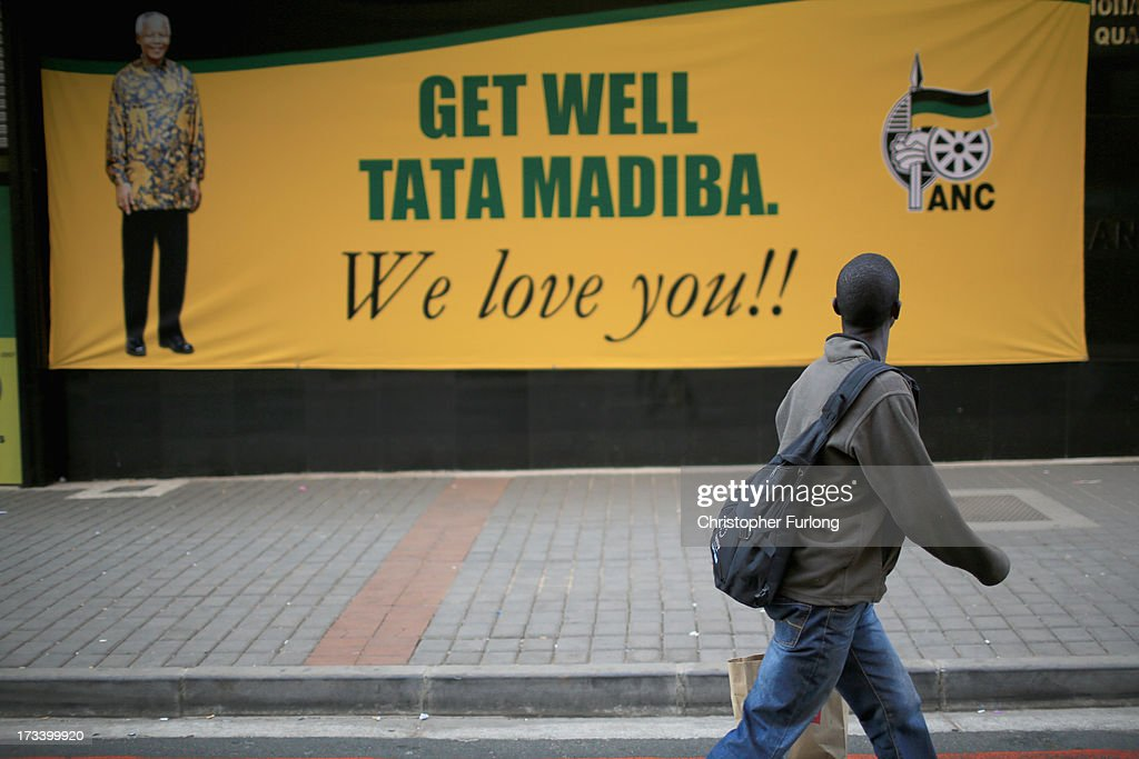 A man walks past a banner supporting ailing Nelson Mandela on July 13, 2013 in Johannesburg, South Africa. Former South African President Nelson Mandela has been hospitalized at the Medi-Clinic Hospital in Pretoria for five weeks. His wife Graca Machel has said she was less anxious about his condition on July 12.